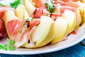 stock photo of melon  - salad of fresh melon with thin slices of prosciutto arugula leaves and balsamic sauce closeup - JPG