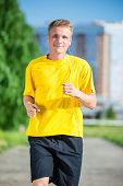 stock photo of jogger  - Running man jogging in city street park at beautiful summer day - JPG