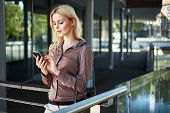 image of natural blonde  - Young blonde lady with a smartphone - JPG