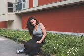 picture of curvy  - Beautiful young curvy girl in tank top sitting in the grass - JPG
