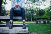 foto of woman boots  - A young woman wearing boots is sitting on a bench in a park - JPG