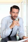 stock photo of sparkling wine  - handsome man drinking a glass of sparkling wine white sitting at the bar with newspaper - JPG