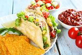 stock photo of tacos  - Tasty taco with nachos chips and vegetables on plate on table close up - JPG