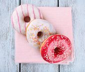 stock photo of donut  - Delicious donuts with icing on napkin on wooden background - JPG
