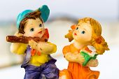 image of flute  - macro photography depicting small statue of a boy playing flute and a girl singing  - JPG