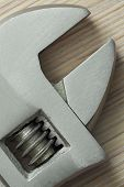 foto of extreme close-up  - adjustable wrench closeup on wooden background - JPG