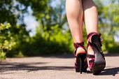 picture of ankle shoes  - Nice female legs in pink shoes walking along the road - JPG