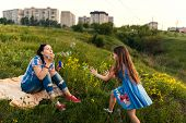 foto of blowing  - Mother and daughter blowing soap bubbles in garden - JPG