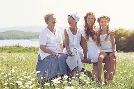 foto of four  - Four generations of beautiful women sitting together in a camomile field and smiling - JPG