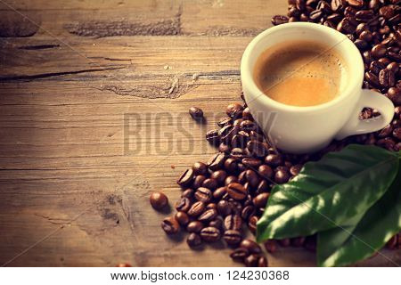 Coffee. Cup Of Espresso Coffee on wooden background decorated with coffee beans and green leaf of co