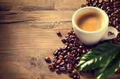 Coffee. Cup Of Espresso Coffee on wooden background decorated with coffee beans and green leaf of co poster