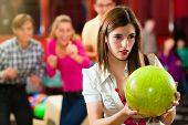Group of four friends in a bowling alley having fun, three of them cheering the one girl in charge t
