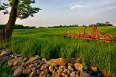 late hour view of farm equipment on grassy hill with rock wall.