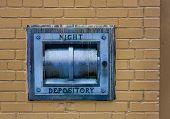 Closeup of locked night depository box on brick wall.