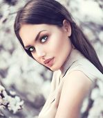 Spring fashion girl outdoors portrait in blooming trees. Beauty Romantic woman in flowers. Sensual L poster