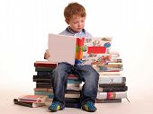 picture of young boy  - young boy sitting on a pile of books reading against a white background - JPG