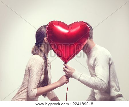 poster of Valentine Couple. Beauty Girl and her Handsome Boyfriend holding heart shaped air balloon and kissin