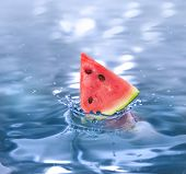 slice watermelon falling in a refreshing drink
