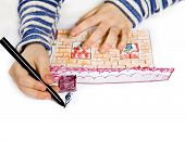 Childrens hand with pencil draws the house , isolated on white background