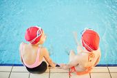 Overview of two girlfriends in swimwear spending time by swimming-pool after school poster