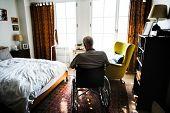 Senior man sitting on the wheelchair alone poster