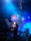 Lead Singer Of Primus Sings On Stage With Blue Lights And Mist Shining On Him
