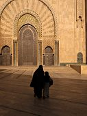 Silhouette Of Woman In Burka And Child Walking In Front Of Mosque
