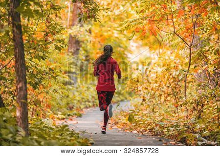poster of Run woman jogging in outdoor fall autumn foliage nature background in forest. Trail running runner a