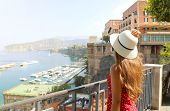 Summer Holiday In Italy. Back View Of Young Woman Holding Her Hat With Sorrento Village And Harbor O poster