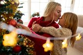 Front view of a young Caucasian woman kissing her young daughter beside the Christmas tree in their  poster