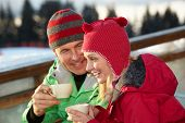 Couple Enjoying Hot Drink In Cafe At Ski Resort