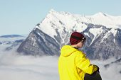 Teenage Snowboarder Admiring Mountain View Whilst On Ski Holiday In Mountains