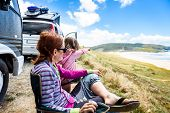 Motorhome Rv Or Campervan Is Parked On A Beach. Family On Vacation Is Sitting Outsides On Camping Ch poster