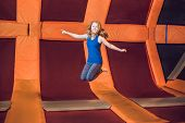 Young Woman Sportsman Jumping On A Trampoline In Fitness Park And Doing Exersice Indoors poster