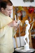 Bildhauer arbeitet aufmerksam auf ein Fragment der Gips-Skulptur im Studio.