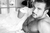 Sexy, Hairy Naked Muscular Man With Sixpack Abs Lying In Bed Covered With Sheet Drinking Coffee poster