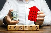 A Man Holds A Red House And A Roll Of Dollars Over The Word Assets. Declaration Income And Taxation, poster