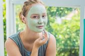 Spa Woman Applying Facial Green Clay Mask. Beauty Treatments. Close-up Portrait Of Beautiful Girl Ap poster