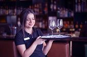 Waitress Carries A Wine Glasses On A Tray To The Client Of The Hotel Bar. Young Bartender Carries Wi poster