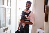 Man Carrying Baby Daughter In Sling Opens Front Door Of House poster
