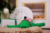 The Baby Is Lying In Christmas Gnome Costume In Christmas Studio. The Costume For The New Year. A Ne poster