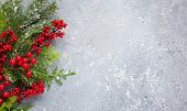 Christmas or winter background with a border of green and frosted evergreen branches and red berries poster