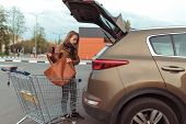 Woman At Shopping Center, Opened Trunk Of A Car, Puts A Shopping Bag In Trunk Of Car, Brown Leather  poster