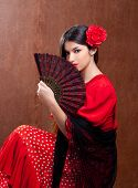 stock photo of frilly  - Flamenco dancer Spain woman gypsy with red rose and spanish hand fan - JPG