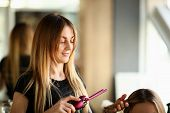 Woman Hairdresser Holding Curling Iron In Hand. Blonde Hairstylist Using Tool For Making Curly Hair. poster
