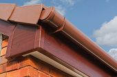 stock photo of gutter  - close up of Brown wood effect PVCu or plastic soffit fascia and guttering on modern new build residential property - JPG
