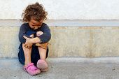 stock photo of sorrow  - poor sad little child girl sitting against the concrete wall - JPG