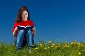 Girl sitting on green meadow reading book