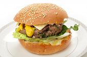 A homemade beefburger patty in a sesame seed bun, with lettuce, arugula (rocket), mustard and a slic