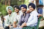 foto of rajasthani  - Group portrait of smiling authentic native indian punjabi sikh men in turban with bushy beard - JPG